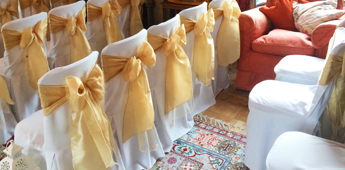 Gold sash bows and white chair covers provide a hint of opulence and luxury