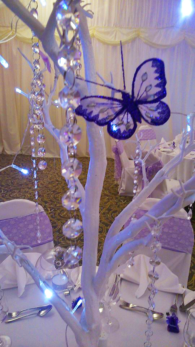 White manzanita wedding tree decorated with purple butterflies and soft LED lighting