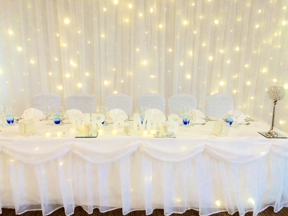 Fairylight backdrop and top table swag by Sophisticated Events
