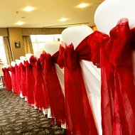 Double layers red organza sash bows over white cotton chair covers