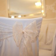 Shimmering pastel salmon pink organza sash bow over crisp white cotton chair covers