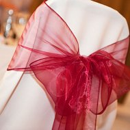 Shimmering cherry red organza bow over an ivory cotton chair cover