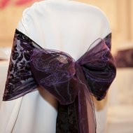 Claret burgandy chiffon and black lace flock overlay double sash over white cotton chair covers