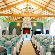 Vibrant teal taffeta with white lace flock overlay double sash bows over white cotton chair covers