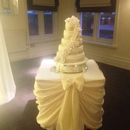 Pristine white drapped taffeta cake table sash with bow